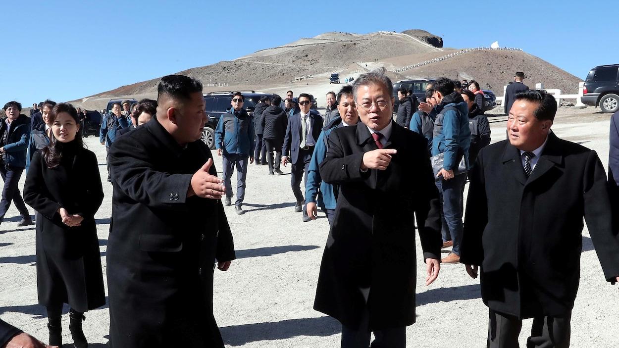 Les deux dirigeants, accompagnés d'une importante délégation, viennent de sortir de voiture.