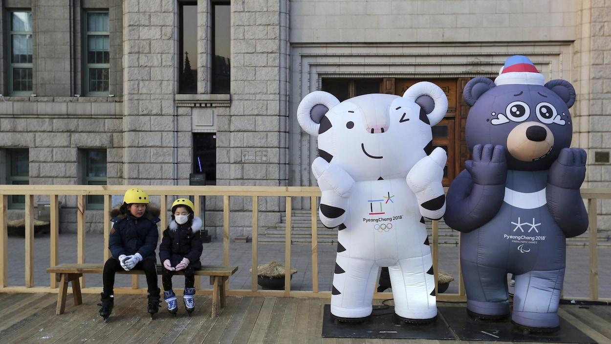 Deux enfants aux côtés de deux mascottes placées près d'une patinoire, à Séoul.