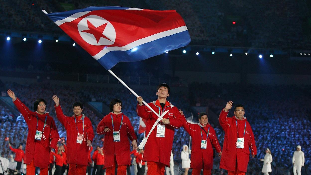 Les athlètes entrent dans le stade vêtus de rouge.