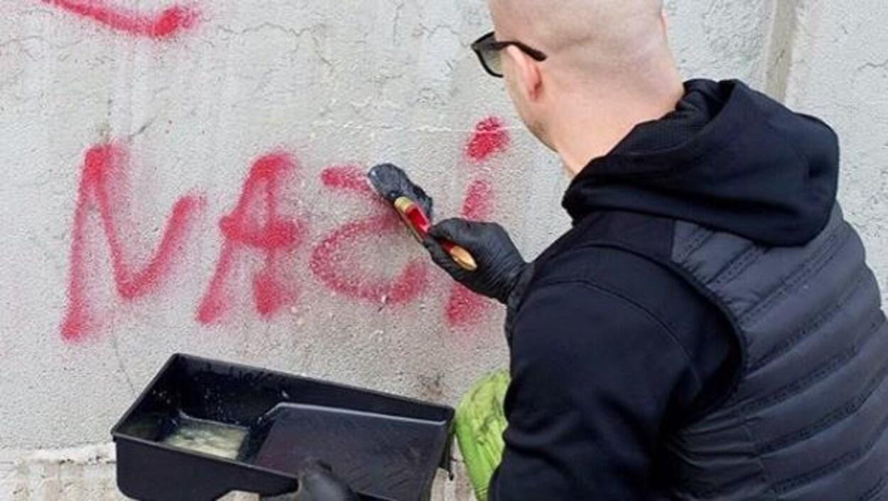 Un homme applique un produit liquide sur un graffiti antisémite afin de l'effacer.