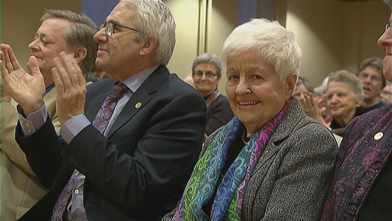La dame dans une assemblée regarde la caméra.