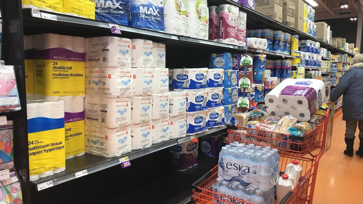 Des étagères avec du papier de toilette et un panier d'épicerie rempli de bouteilles d'eau, de papier de toilette et de pain.