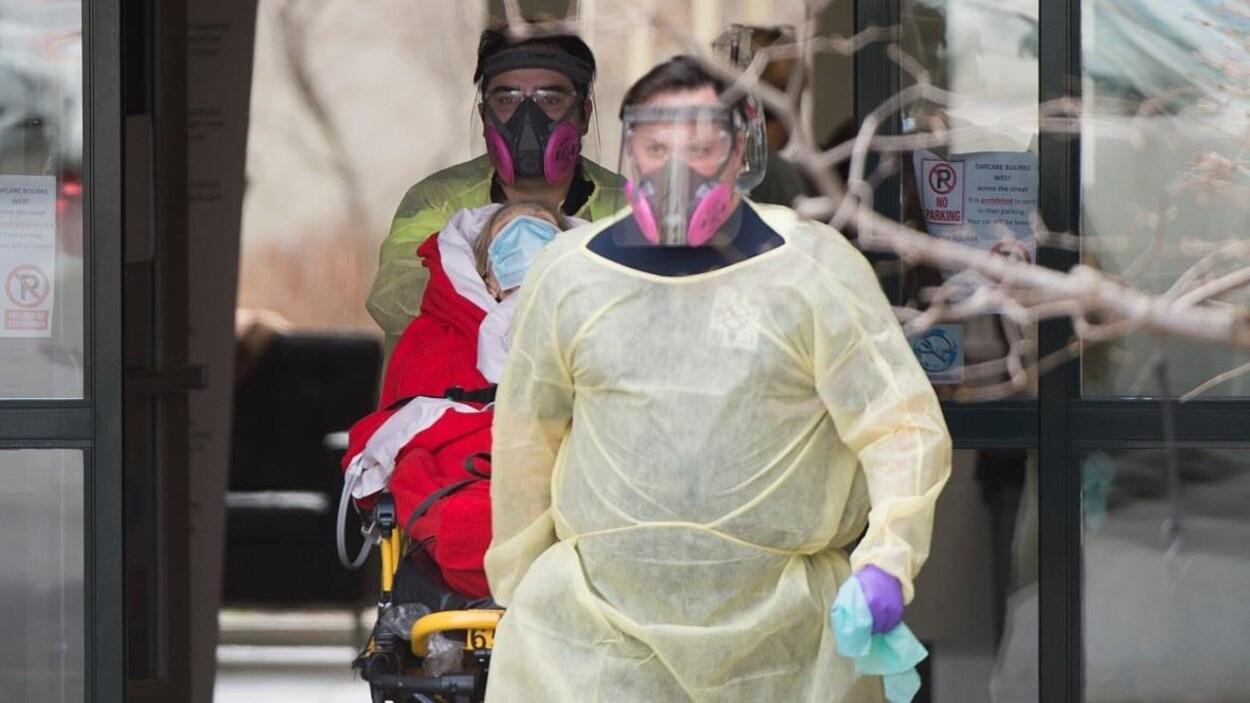 Des travailleurs paramédicaux transportent un patient.