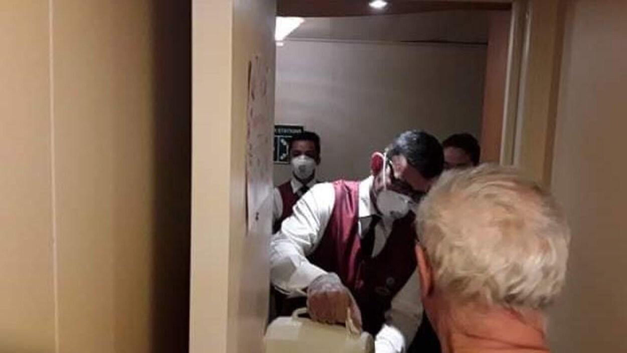 Du personnel d'un navire de croisière verse du café à un homme dans sa cabine.
