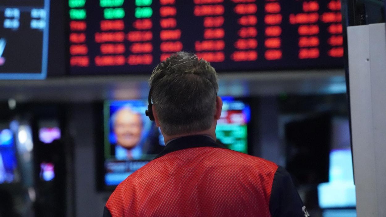 Un courtier regarde les résultats de la Bourse sur un tableau d'affichage numérique.