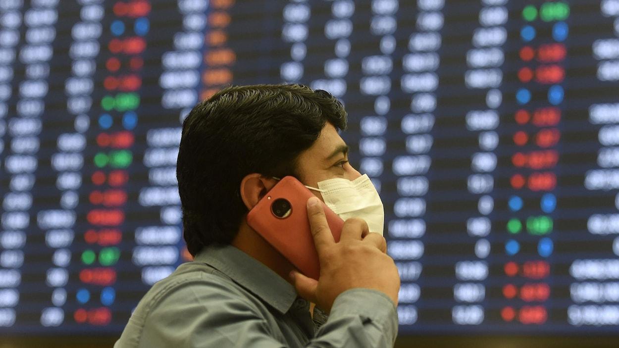 Un investisseur portant un masque parle au téléphone à la Bourse du Pakistan.