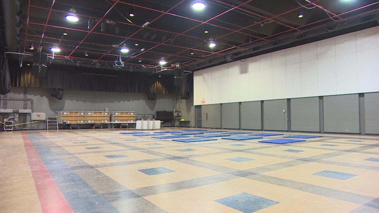 Une grande salle avec des matelas sur le sol.