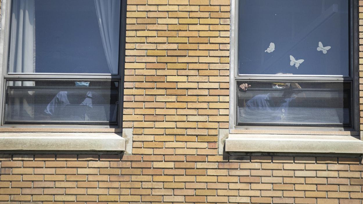 Deux personnes près d'une fenêtre ouverte d'un établissement.