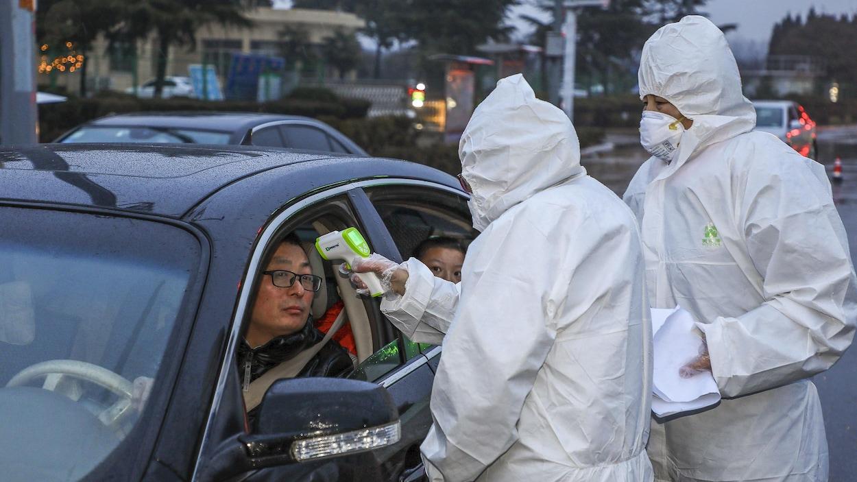 Deux hommes en combinaison de protection mesurent avec un scanner la température d'un automobiliste.