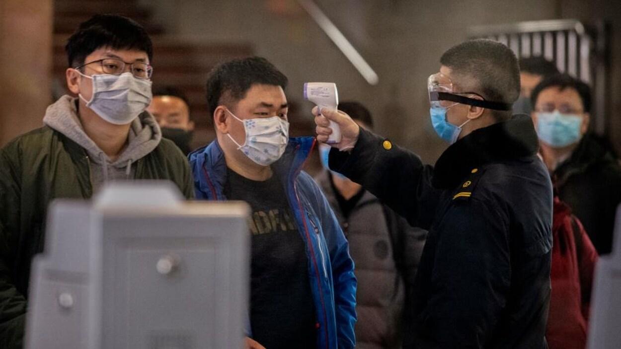 Un membre des services de sécurité mesure la température d'hommes portant des masques respiratoires.
