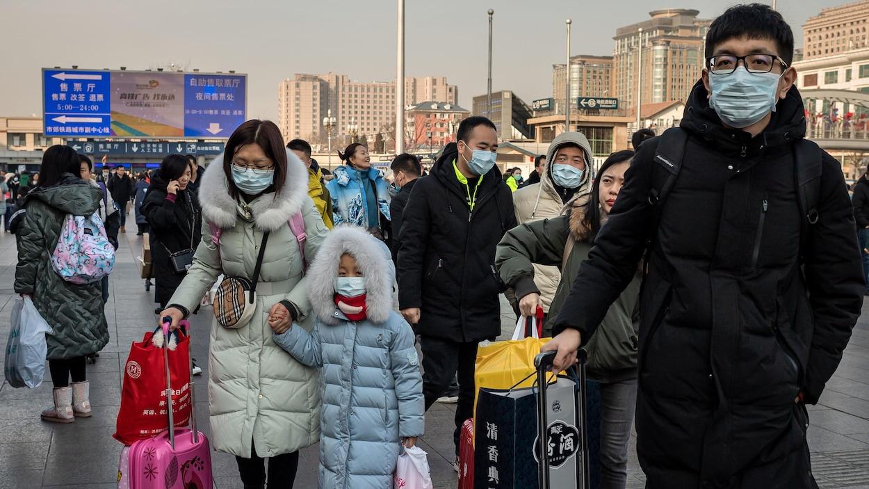 Plusieurs personnes tenant des valises portent des masques respiratoires.