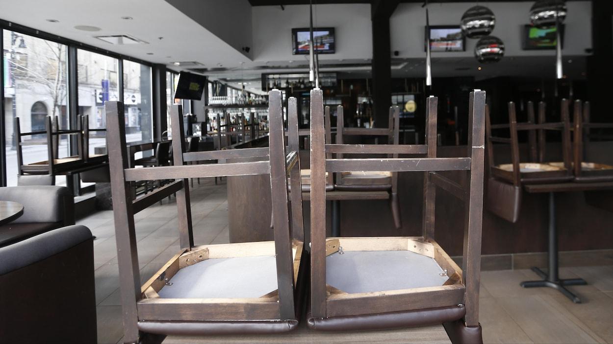 Des chaises retournées sur des tables dans un restaurant fermé.