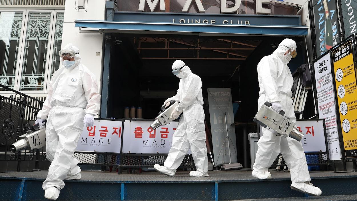 Des agents de quarantaine pulvérisent des désinfectants devant une boîte de nuit dans le quartier d'Itaewon, à la suite de l'éclosion récente à Séoul.
