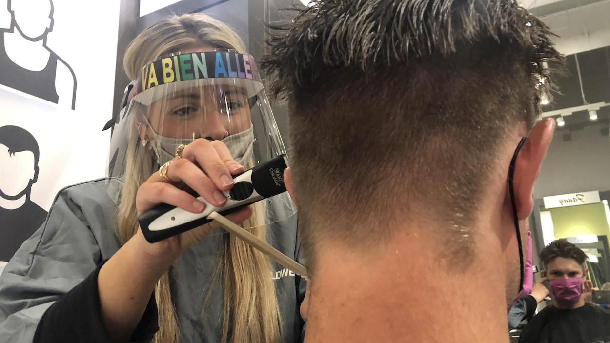 Une coiffeuse, portant un équipement de protection contre le coronavirus, rase les cheveux d'un client.