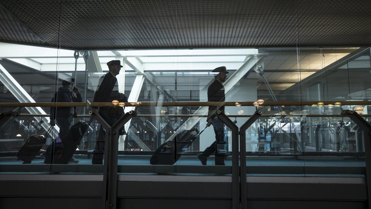 Des pilotes et un passager marchent à l'intérieur de l'aéroport de Vancouver.