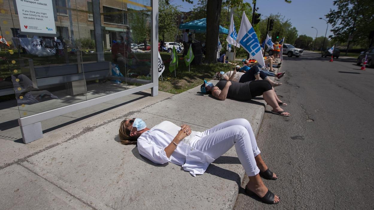 Du personnel infirmier est couché sur le trottoir de manière symbolique lors d'une manifestation devant un établissement, en plein jour.