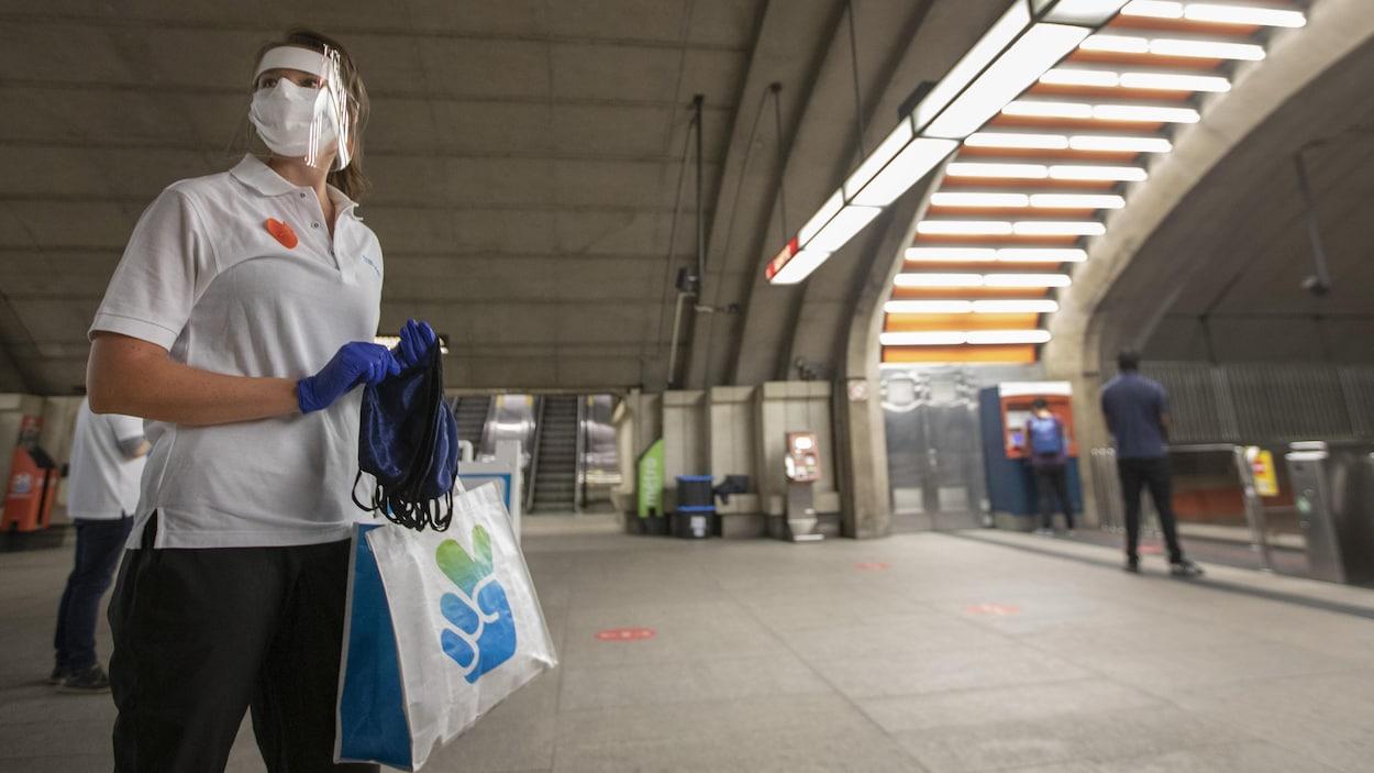 Une femme portant un masque et une visière distribue des masques dans une station de métro de Montréal.