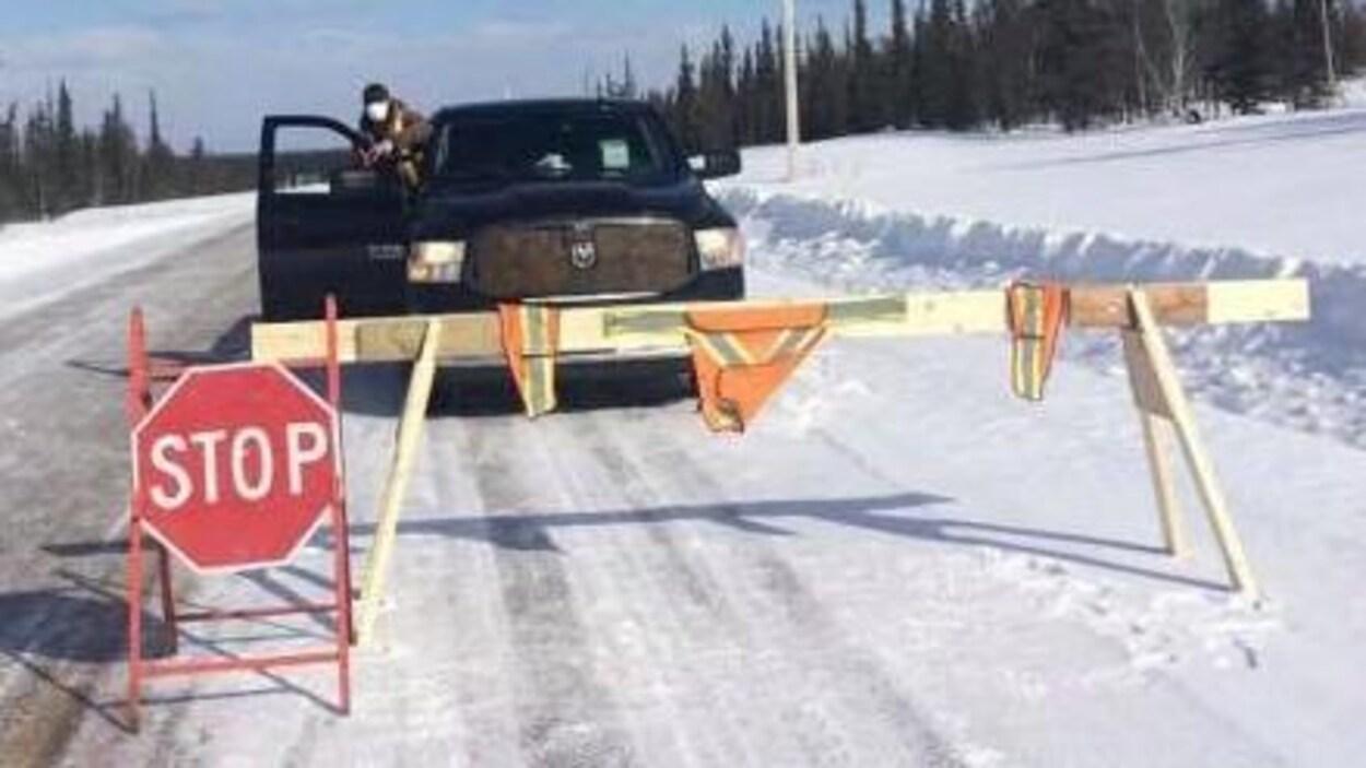 Un homme qui porte un masque chirurgical est debout dans sa camionnette lors d'un contrôle routier le long d'une route enneigée.