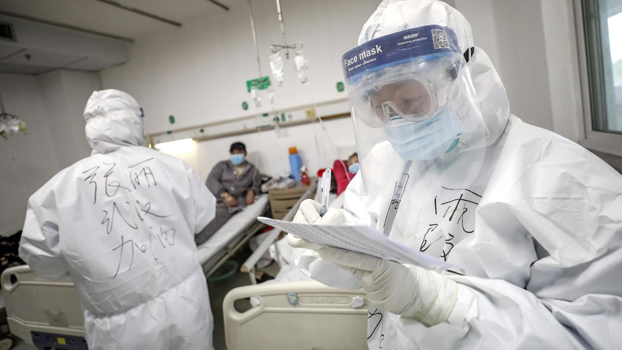 Deux employés dans un hôpital, vêtus de combinaison de protection, avec deux patients.