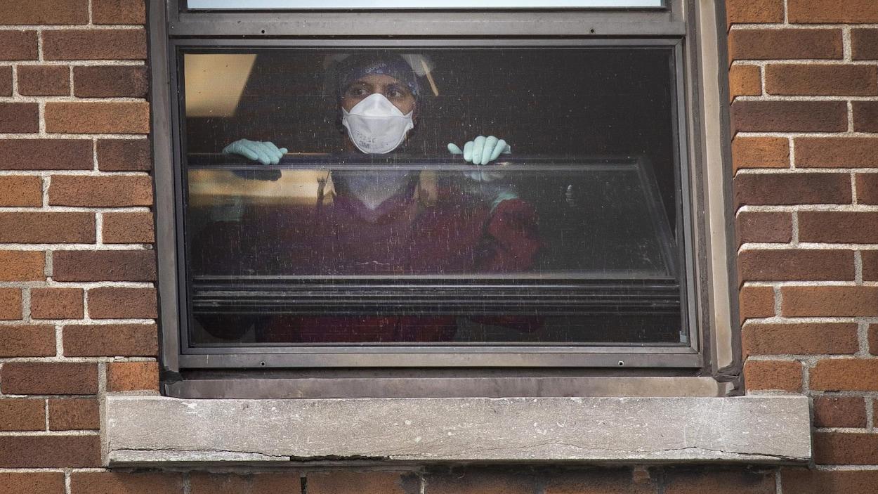 Une employée à la fenêtre d'un hôpital.