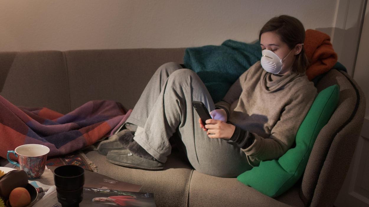 Une jeune femme portant un masque et sa mère assises sur un canapé.
