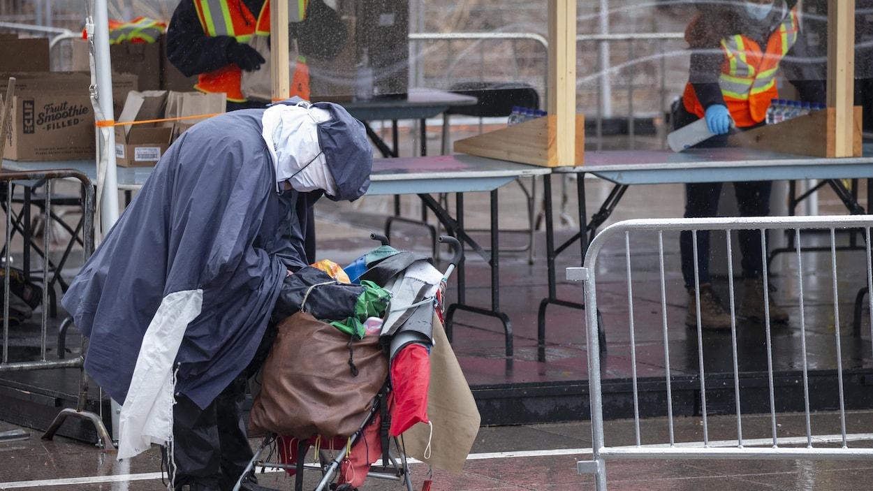 Une personne itinérante fouille dans ses sacs devant un comptoir de distribution d'aliments au centre-ville de Montréal.