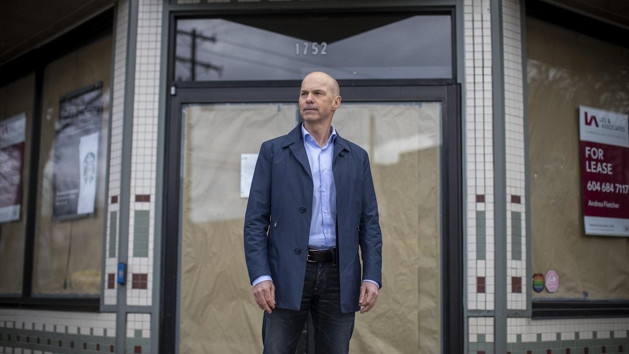 un homme debout devant un magasin fermé de Vancouver.