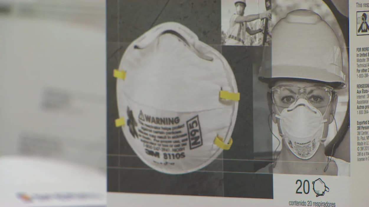 La photo d'une boîte avec un masque blanc et rond. Sur la boîte, il y a aussi l'image d'une femme qui porte le masque, un casque blanc et des lunettes transparentes.