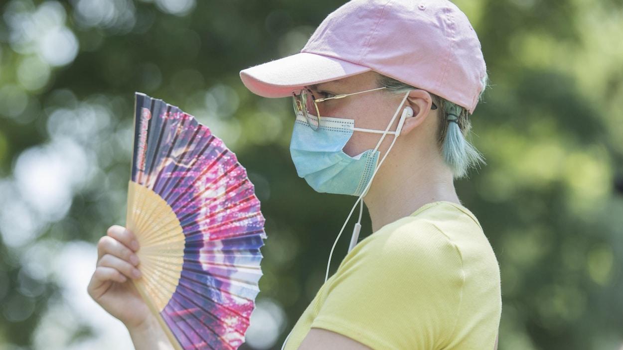 Une femme porte un masque dans un parc et se rafraîchit avec un éventail.