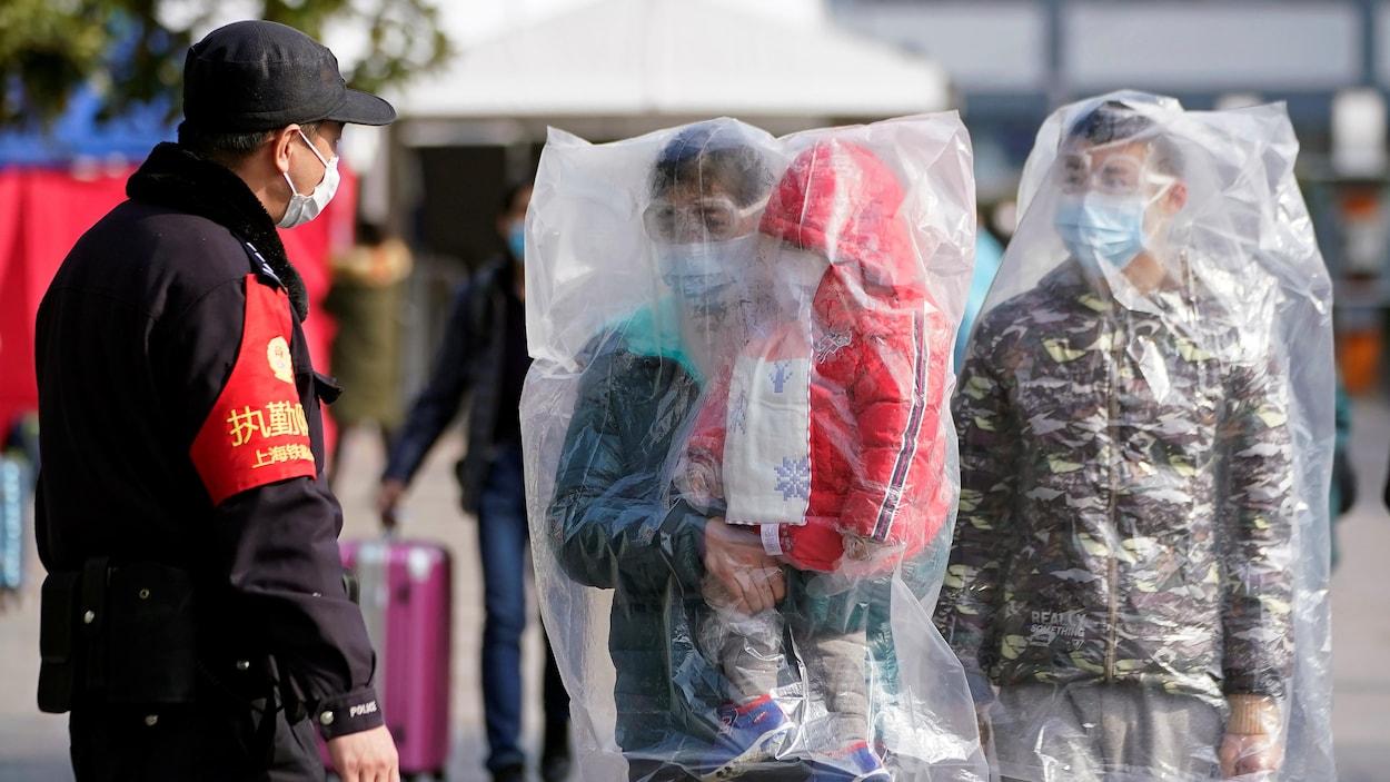 Un agent en uniforme et deux hommes, dont un porte un enfant, sont couverts de sacs en plastique.