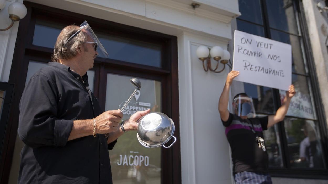 Un homme tient une casserole et un autre une pancarte durant une manifestation.