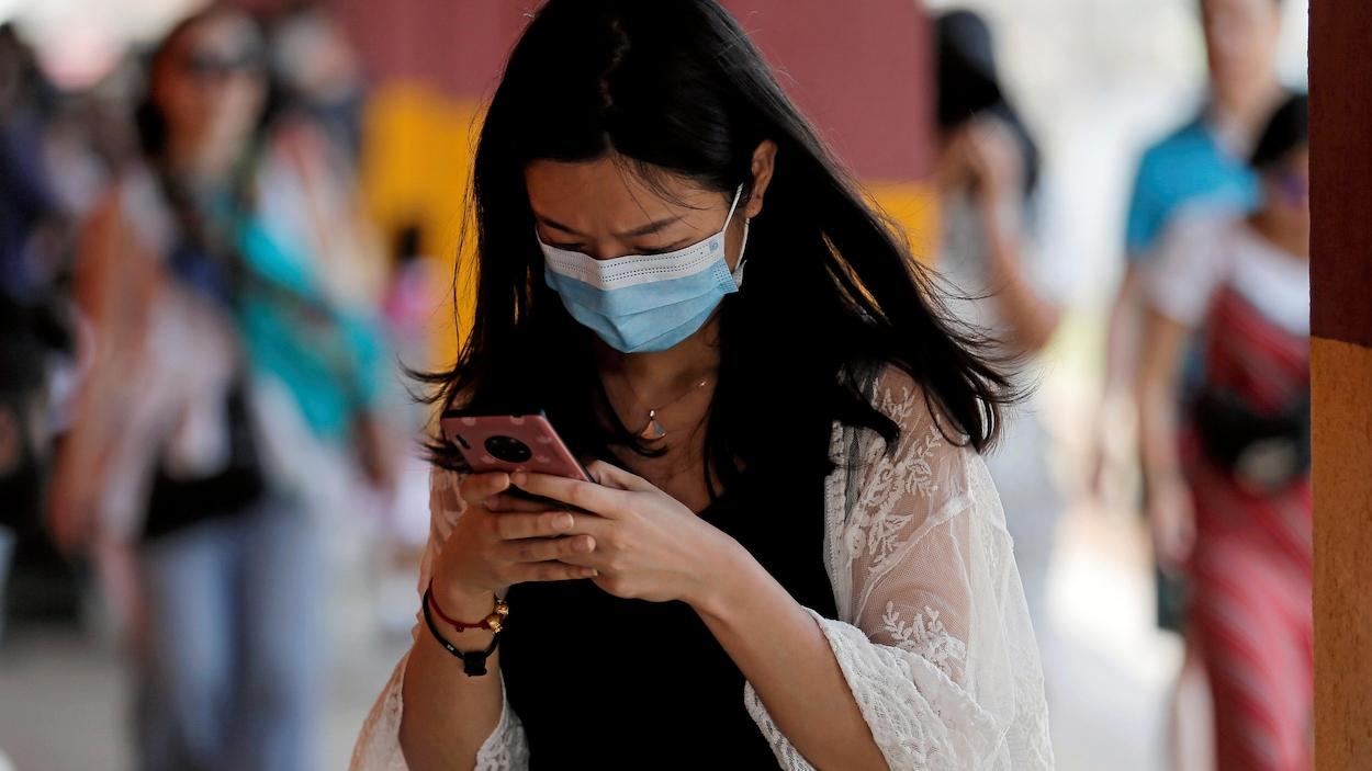 Une femme regarde son telephone. Elle porte un masque facial pour se protéger du coronavirus.