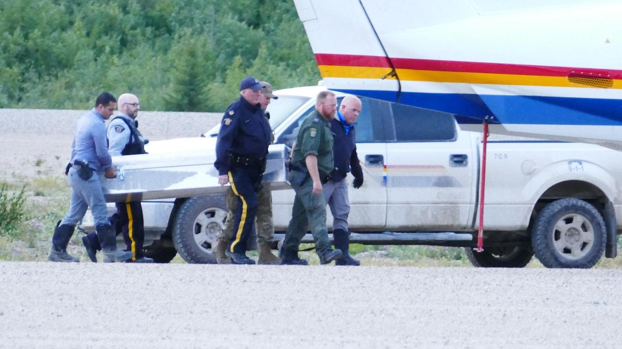 Des agents de la GRC transportent un cercueil près d'un avion.