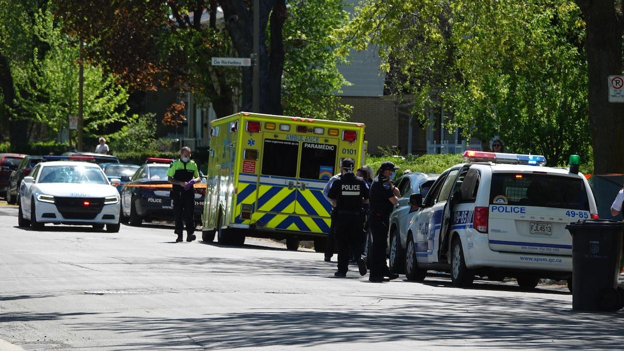 Des voitures de police et une ambulance dans une rue au périmètre sécurisé.
