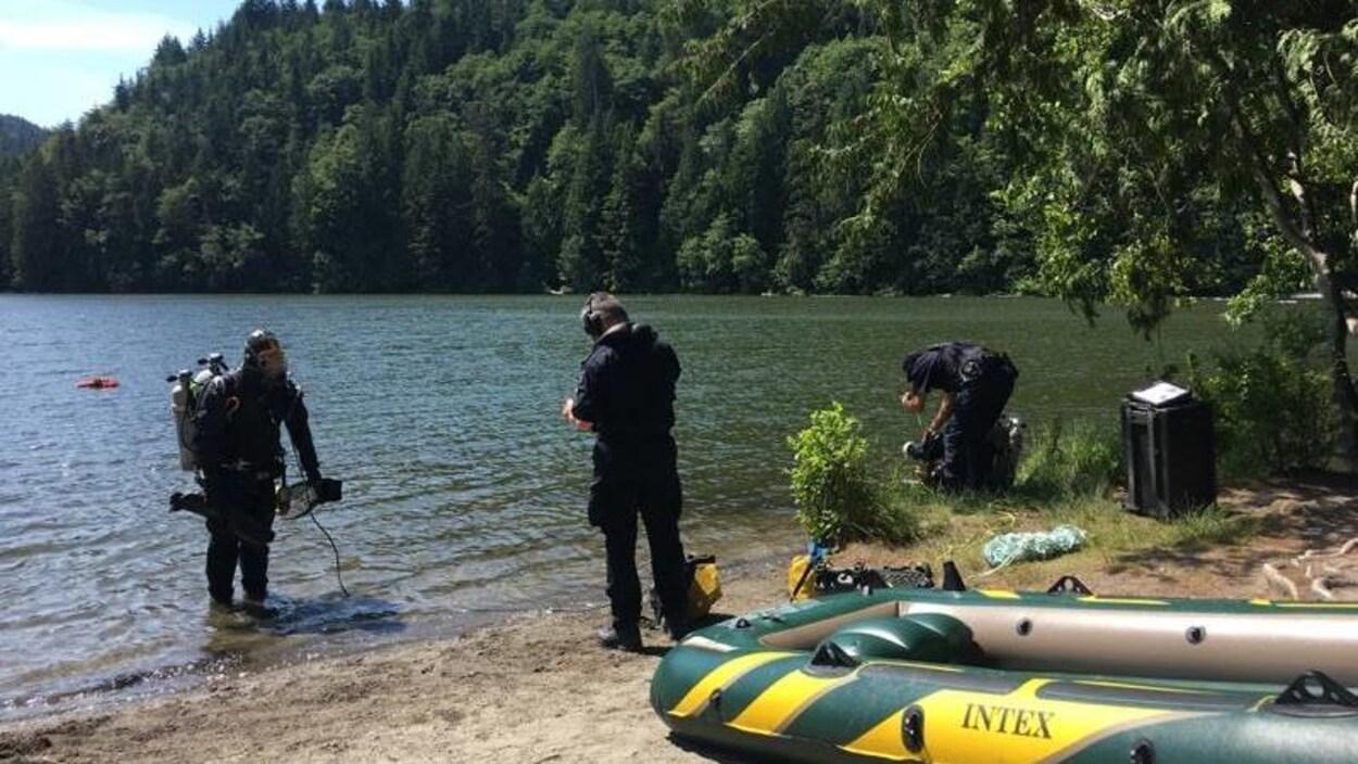 Trois plongeurs de la GRC au bord du lac en plein soleil.