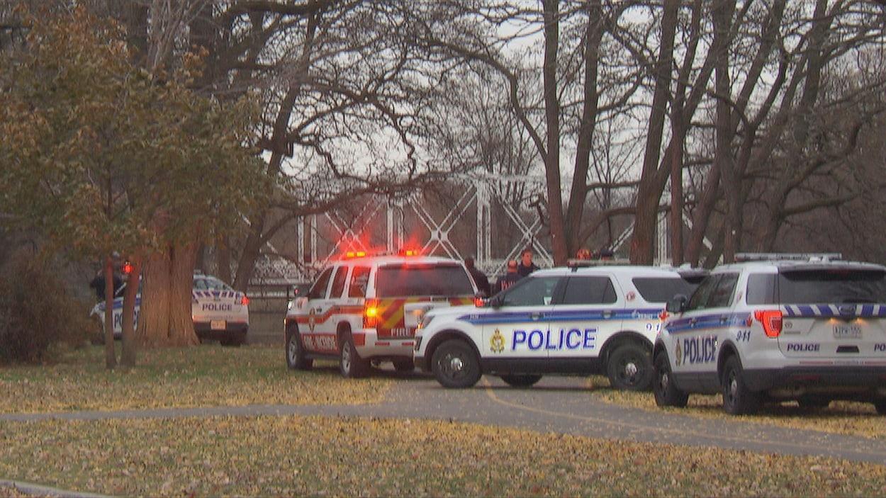 Des voitures de police et du Service des incendies d'Ottawa stationnées dans un parc devant un pont