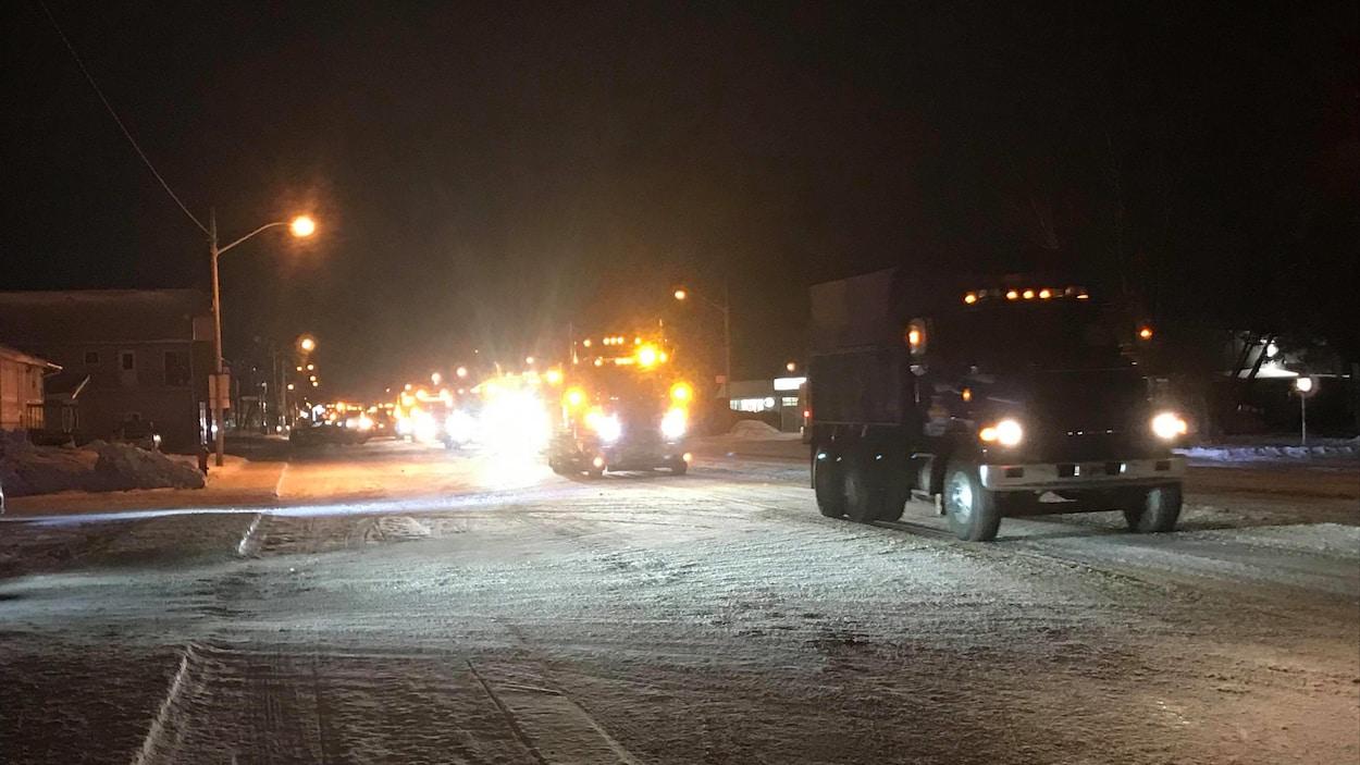 Des camions circulent sur une rue enneigée, en soirée.