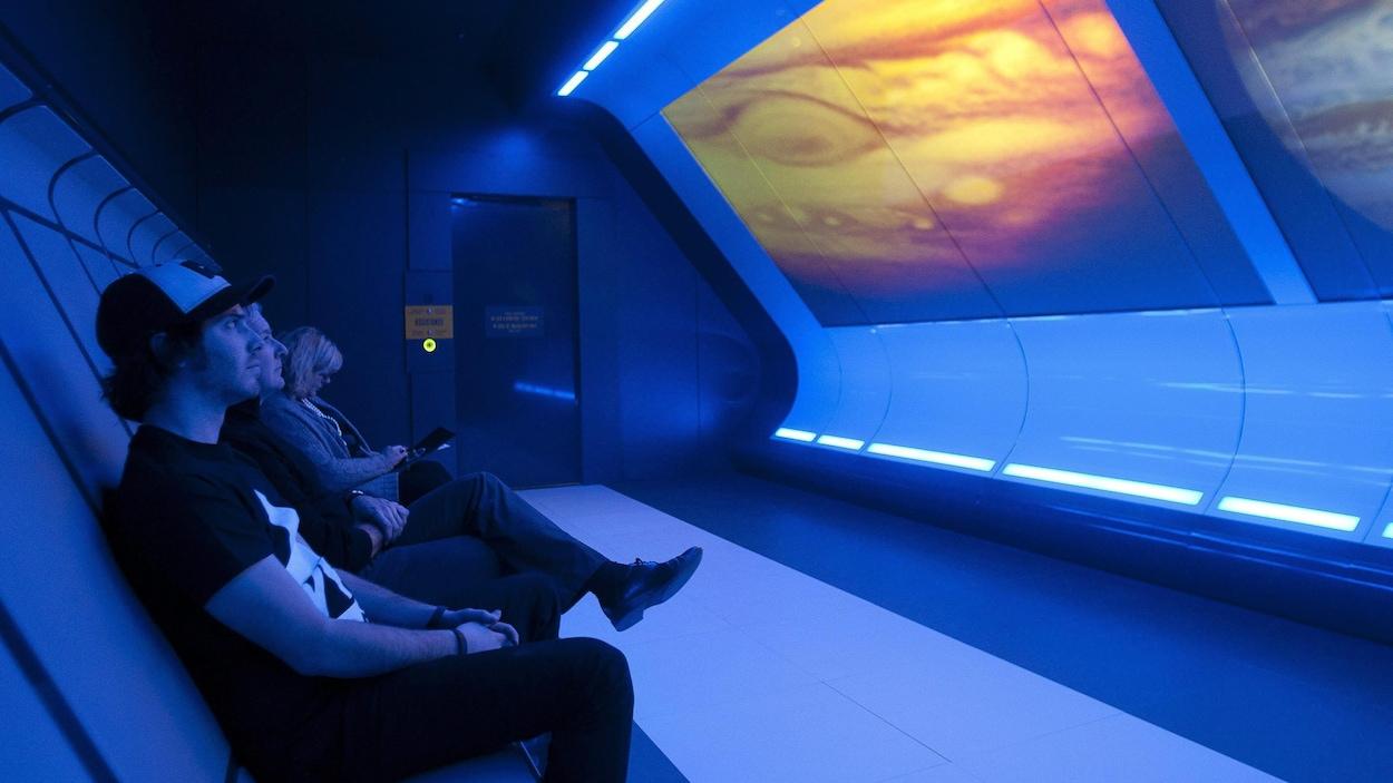 Trois personnes regardent une exposition sur le Cosmo.