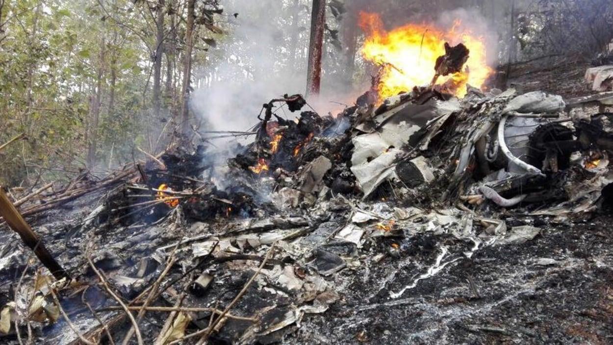 Une carcasse d'avion qui brûle encore est photographiée dans la forêt. Les restes de l'appareil sont éparpillés sur le sol en pente.