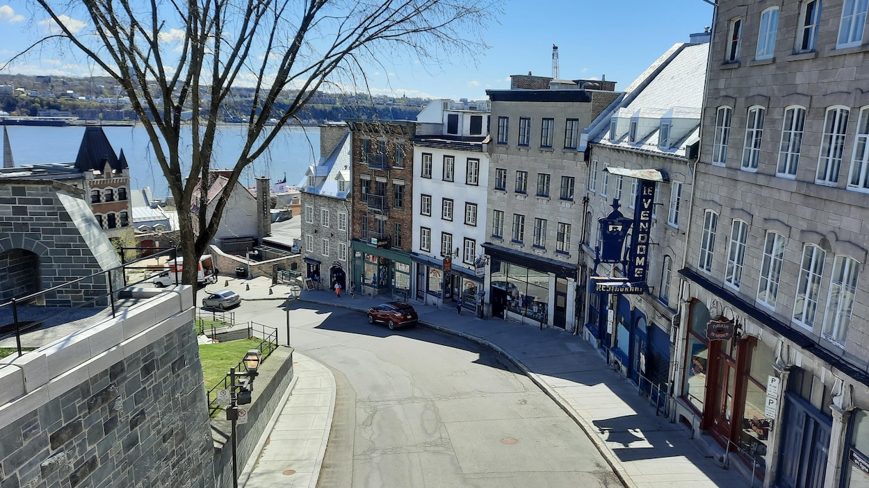 La côte de Montagne serpente en direction de la basse-ville. On voit l'embranchement de l'escalier Casse-cou vers la droite, et on devine les installations du port de Québec tout en bas, avec le fleuve au loin.