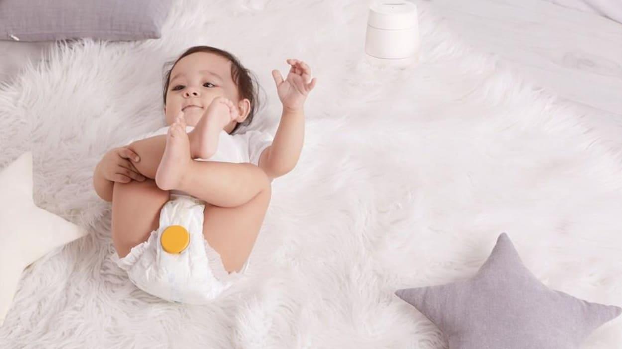 Un bébé porte une couche équipée d'un capteur Monit jaune.