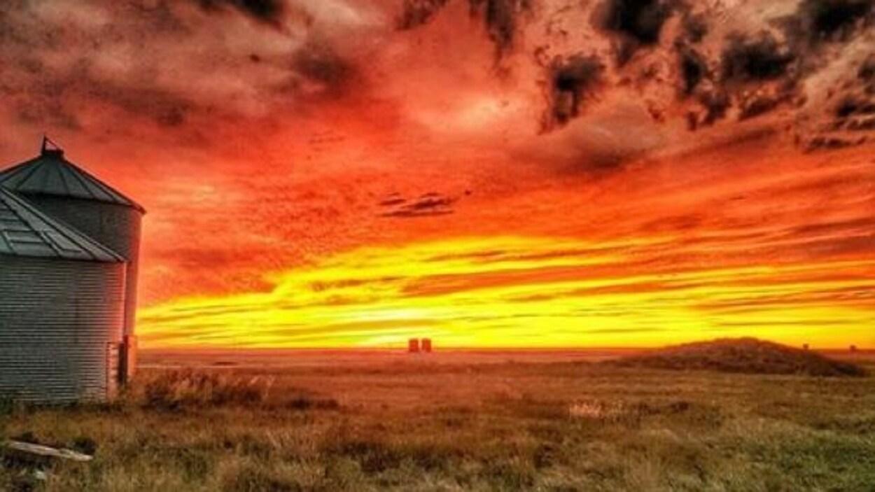 Coucher de soleil sur une ferme : le ciel semble être en feu avec des couleurs vives, jaune et rouge, des nuages gris et deux silos à grain