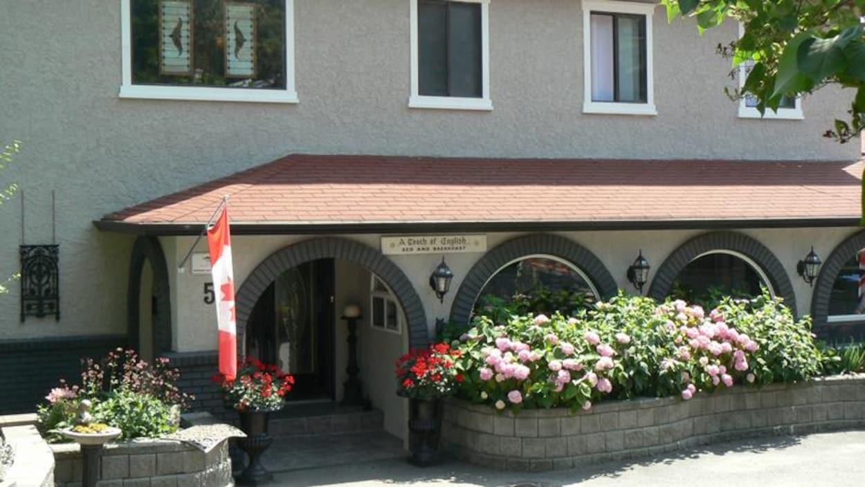 Devanture d'un gîte touristique décoré avec de magnifiques fleurs et un drapeau du Canada.