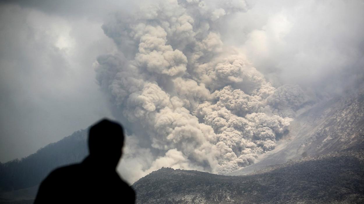 Un homme, de dos, observe une coulée pyroclastique.