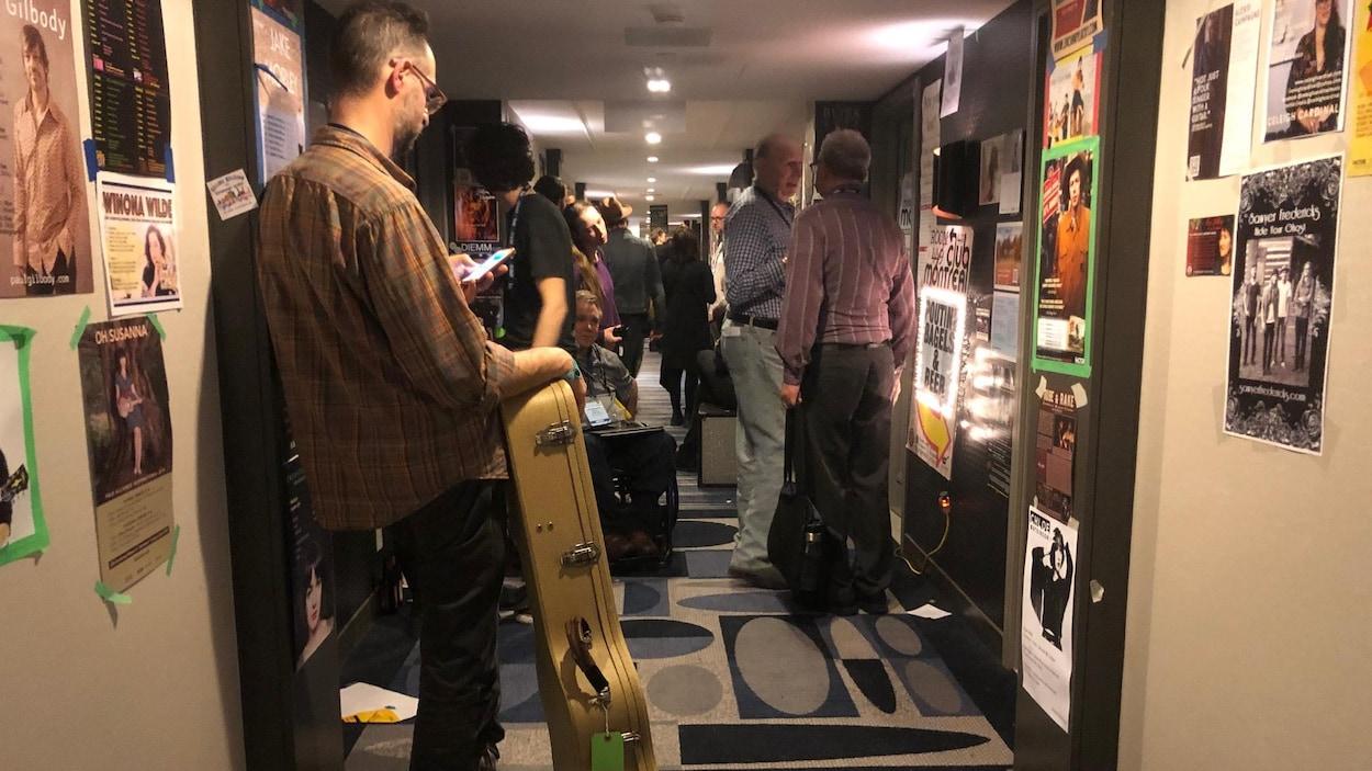 Les murs du couloir sont couverts d'affiches de musiciens, et le couloir et plein de monde.