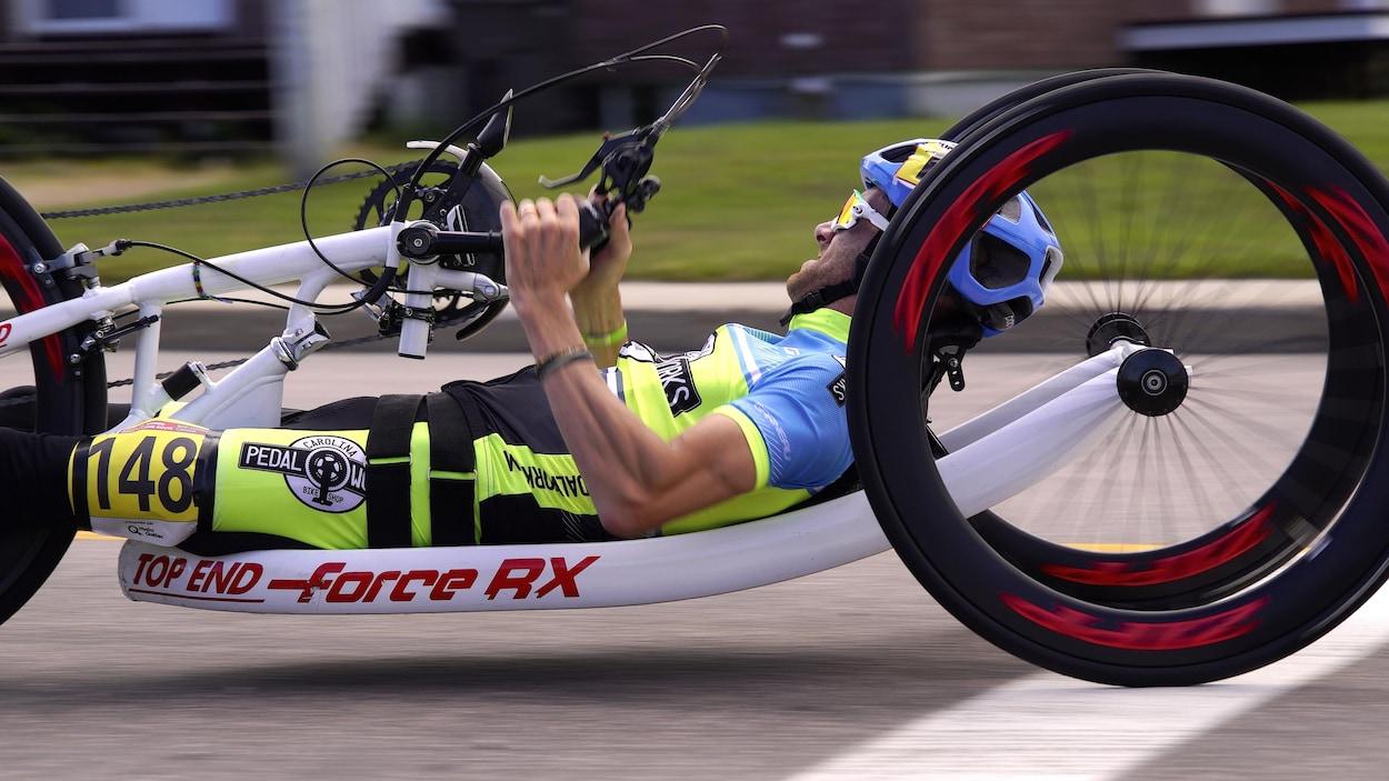 Un athlète couché sur son vélo actionné par ses mains