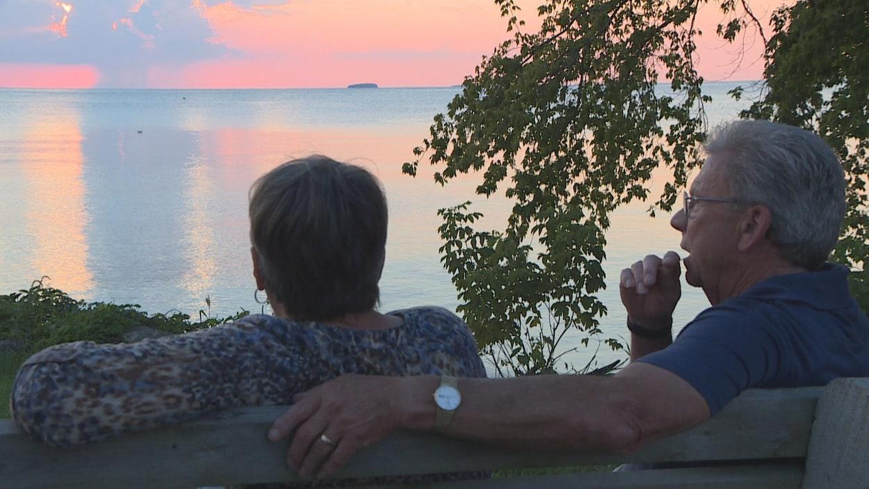 Un homme enlace une femme sur un bas en regardant un bord d'eau.