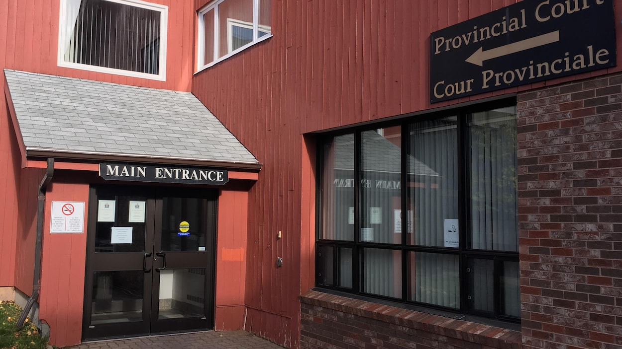 Une porte d'entrée d'un édifice avec une affiche identifiant la Cour provinciale