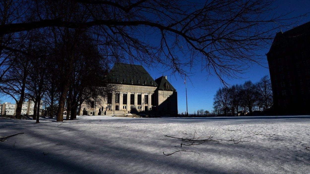 La Cour suprême du Canada en hiver sur fond de ciel indigo.