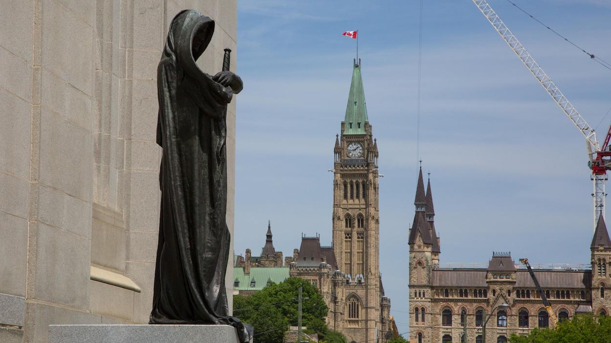 Au premier-plan, l'édifice de la Cour suprême avec une statue représentant la justice, et en arrière-plan des édifices du Parlement canadien.